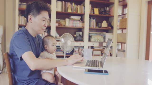 4k vater arbeitet am laptop mit baby zu hause - genderblend stock-videos und b-roll-filmmaterial
