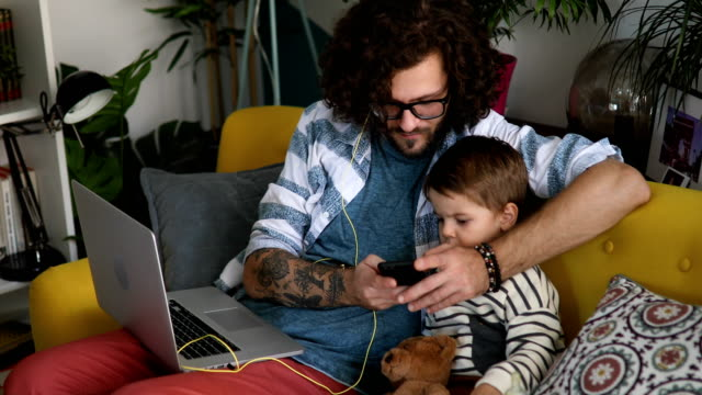 father working on laptop and playing cartoons to his son on smartphone - parent stock videos & royalty-free footage