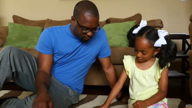 ms zi zo father working on puzzle with young daughter in living room - puzzle stock videos & royalty-free footage