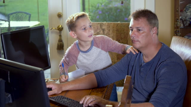 vídeos de stock e filmes b-roll de father working, son doing schoolwork at home - 50 54 years