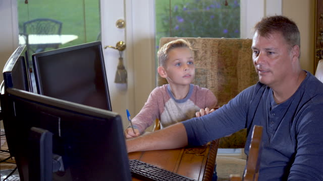 father working, son doing schoolwork at home - 8 9 years stock videos & royalty-free footage