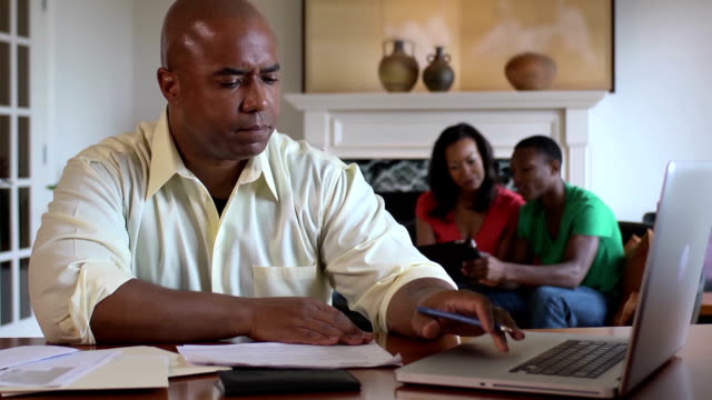 Father Works on Home Finances with Family in Background