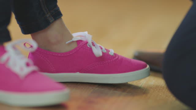 stockvideo's en b-roll-footage met cu. father's hands tie laces of daughter's pink shoes. - schoen