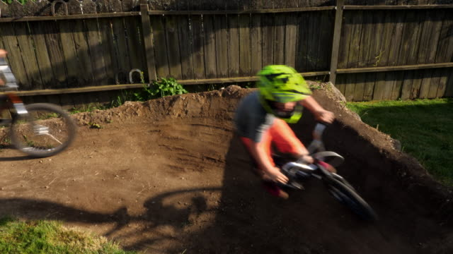 vídeos y material grabado en eventos de stock de ms fathers riding bmx bikes with sons on backyard dirt track on summer evening - familia con cuatro hijos