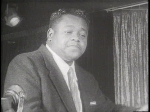 stockvideo's en b-roll-footage met fats domino plays piano and taps his foot stopping for an interview about a goodwill trip to the soviet union - 1956