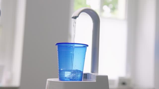 水で青い使い捨てカップを満たす蛇口 - cup点の映像素材/bロール