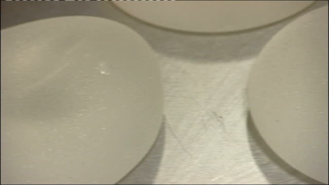 government advice may be flawed tx close shots of breast implants on table - brustimplantat stock-videos und b-roll-filmmaterial