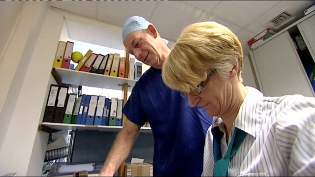 government review recommends no routine removal of implants Peter Arnstein talking with female colleague in clinic office Close shot of brest implant...