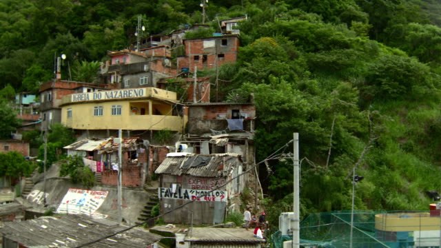 vidéos et rushes de favela, impoverished neighborhood buildings, structures on green hillside, run-down, deteriorating, decaying walls, portuguese words graffiti,... - corcovado