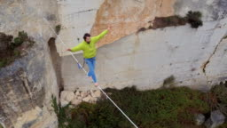 AERIAL: Fearless guy balancing on bouncy slackline tensioned over deep quarry