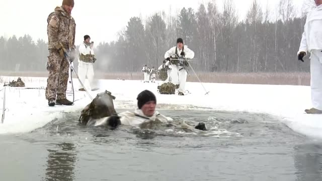 fears over trump's commitment to nato and effects on relationship with russia; latvia: ext various of us troops in winter camouflage clothing walking... - bagnato bildbanksvideor och videomaterial från bakom kulisserna