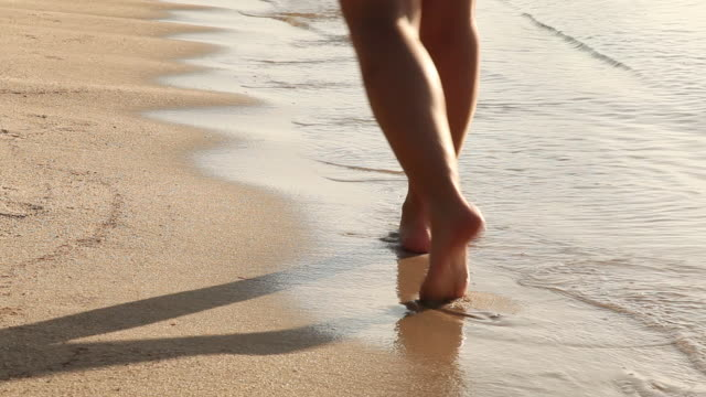 MS Feat of young woman walking alongshore line at dawn with small waves coming to shore / Placencia, Stann Creek, Belize