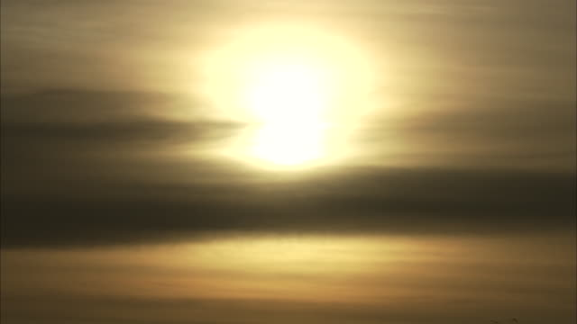 a feathery sun rests on the horizon. - illusion stock videos & royalty-free footage