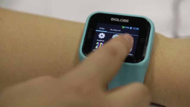 vidéos et rushes de features of biglobe incs internet connected device with a built in sim card is displayed by an attendant, an attendant wearing biglobe incs internet... - montre intelligente