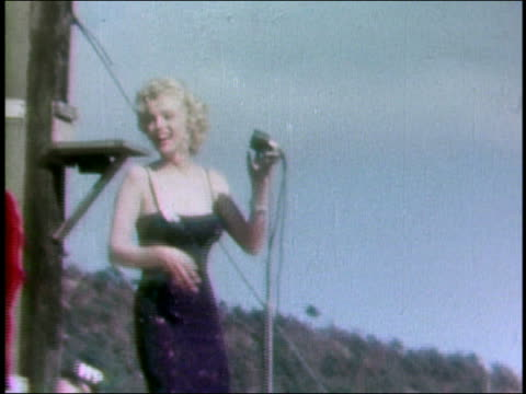 stockvideo's en b-roll-footage met february 18 1954 shaky medium shot marilyn monroe onstage / blowing kiss / korea - marilyn monroe