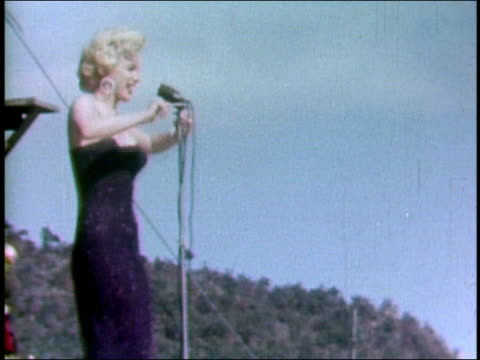 february 18 1954 shaky medium shot marilyn monroe singing and dancing onstage / saxophonist in background / korea - korean war stock videos & royalty-free footage