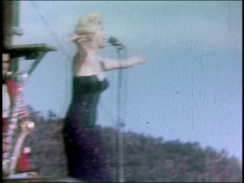 february 18 1954 shaky medium shot marilyn monroe singing onstage / saxophonist in background / korea - woodwind instrument stock videos and b-roll footage