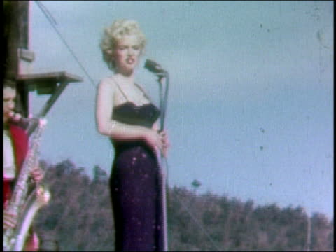 stockvideo's en b-roll-footage met february 18 1954 shaky medium shot marilyn monroe singing onstage / saxophonist in background / korea - marilyn monroe