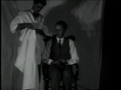 vidéos et rushes de february 2, 1931 ms man sitting in wooden chair and barber placing smock over torso of man / portland, oregon, united states - 1931
