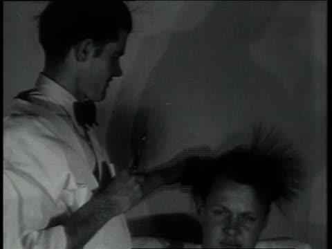 vídeos de stock, filmes e b-roll de february 2, 1931 montage barber cutting man's hair using static electricity / portland, oregon, united states - cabelo assanhado