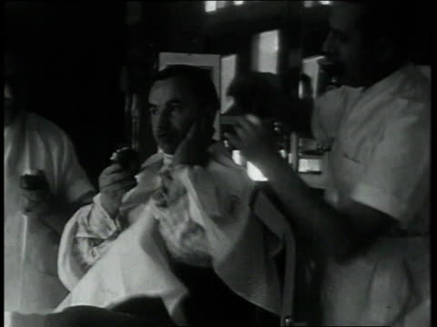 february 2, 1931 montage barber cutting man's hair while he eats an apple / portland, oregon, united states - barber chair stock videos & royalty-free footage