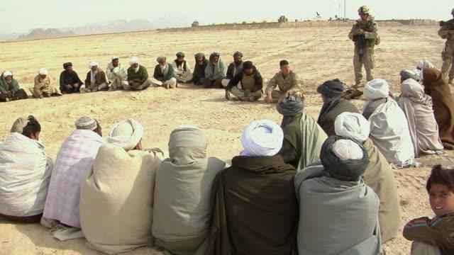 stockvideo's en b-roll-footage met february 2009 ws group of afghani people and soldiers having discussion outdoor / bakwa farah province afghanistan - in kleermakerszit