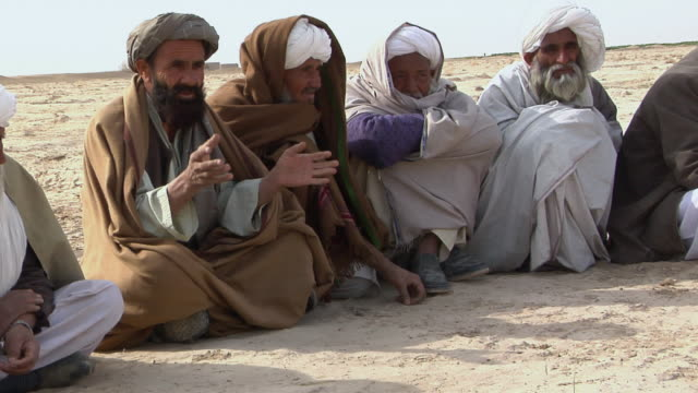 february 2009 ms group of afghani people having discussion outdoor / bakwa farah province afghanistan - legs crossed at ankle stock videos and b-roll footage