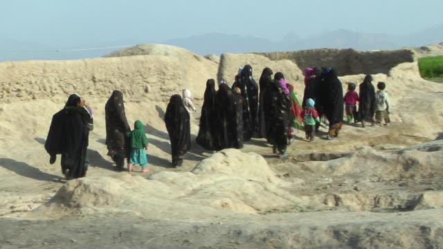 february 2009 ws pan group of women wearing burkha walking in desert / bakwa farah province afghanistan - ムラがある点の映像素材/bロール