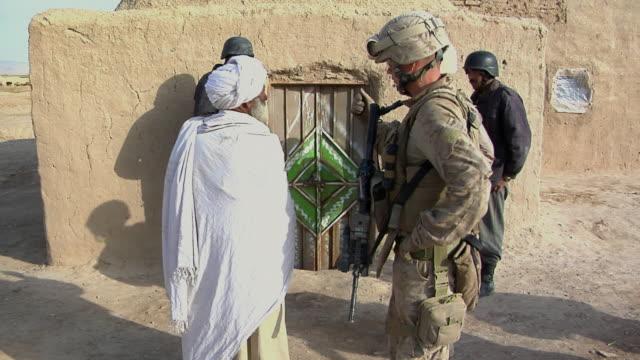 vídeos de stock, filmes e b-roll de february 2009 police officers investigating the rural residence / bakwa, farah province, afghanistan - civil