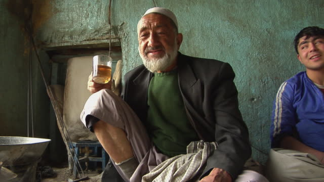 february 2009 senior man drinking tea at home / kabul, afghanistan - provinz helmand stock-videos und b-roll-filmmaterial