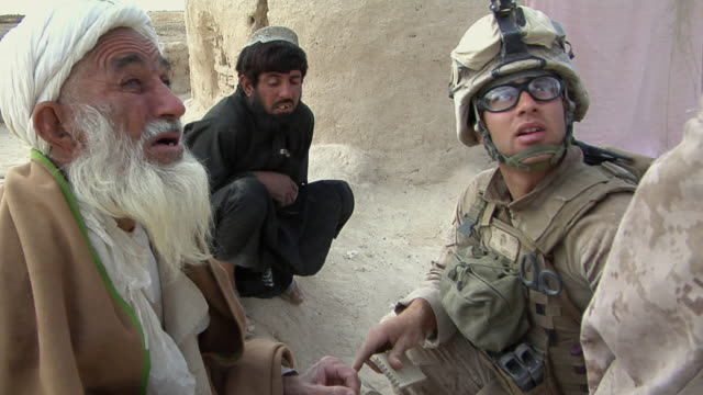 february 2009 cu pan zi tu td soldiers talking to afghani man / bakwa farah province afghanistan - heranzoomen stock-videos und b-roll-filmmaterial