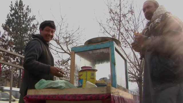february 2009 ms street vendors preparing food and afghan man eating / kabul afghanistan - kabul stock videos and b-roll footage
