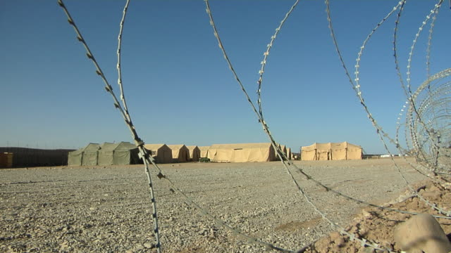 february 2009 ws tent house of soldiers and barbed wire fence in foreground / kabul afghanistan - campo militare video stock e b–roll