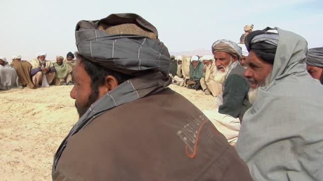 stockvideo's en b-roll-footage met february 2009 ws view of afghani civilians sitting / bakwa farah province afghanistan - in kleermakerszit
