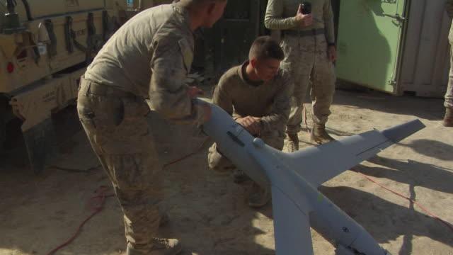 february 2009 ms view of soldiers examining uav / bakwa farah province afghanistan - unbemanntes luftfahrzeug stock-videos und b-roll-filmmaterial