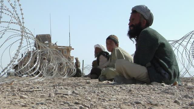 february 2009 ms workers making barbed wire fence / bakwa farah province afghanistan - korslagda ben bildbanksvideor och videomaterial från bakom kulisserna