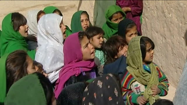 february 2010 afghan children during lesson at school for girls and itn reporter watching - afghanistan stock videos & royalty-free footage