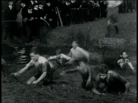 february 23, 1933 montage eton students leaping into water-filled ditch and crawling out on the opposite side during cross-country race / united kingdom - eton berkshire stock videos and b-roll footage