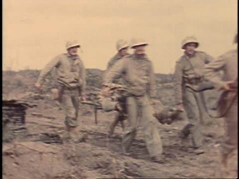 february 23, 1945 montage soldiers carrying wounded man on a stretcher / iwo jima, japan - battaglia di iwo jima video stock e b–roll