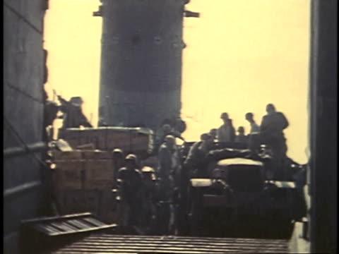 february 23, 1945 montage troops unloading supplies of a ship / iwo jima, japan - battaglia di iwo jima video stock e b–roll