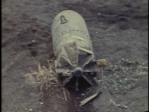 february 25 1945 montage men pulling live japanese aerial bomb across sandy ground with hook and chain attached to rope with crank on military jeep /... - schlacht um iwojima stock-videos und b-roll-filmmaterial