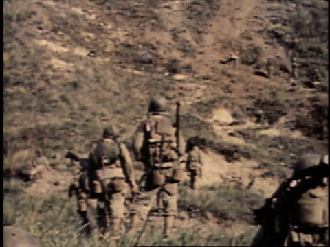 february 26 1945 ha men walking through field and up a hill carrying in uniforms and with guns / iwo jima japan - schlacht um iwojima stock-videos und b-roll-filmmaterial