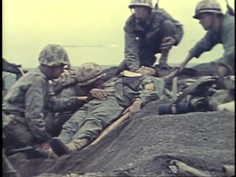 february 26, 1945 montage soldiers carrying wounded man on a stretcher / iwo jima, japan - battaglia di iwo jima video stock e b–roll