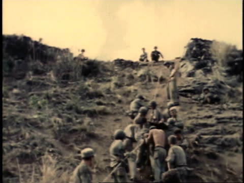 February 26 1945 LA Soldiers attempting to lower injured soldier down hill / Iwo Jima Japan