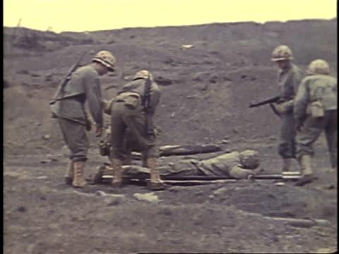 february 26, 1945 soldiers carry wounded man on a stretcher / iwo jima, japan - battaglia di iwo jima video stock e b–roll
