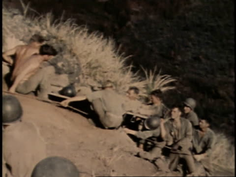 stockvideo's en b-roll-footage met february 26 1945 ha soldiers using a rope up a steep hill to help lower and injured man on a stretcher down to the bottom / iwo jima japan - laten zakken