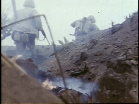 February 26 1945 WS Soldiers walking over burning body / Iwo Jima Japan