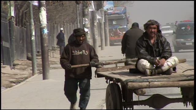 february 28 2009 ts worker pushing passenger in a cart on the sidewalk / kabul afghanistan - 牛車点の映像素材/bロール