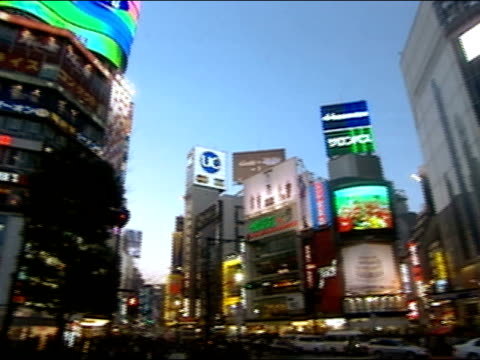 february 3, 2004 low angle circular pan of buildings with electronic billboards lit up at dusk in harajuku district / tokyo, japan - 2004 stock videos and b-roll footage
