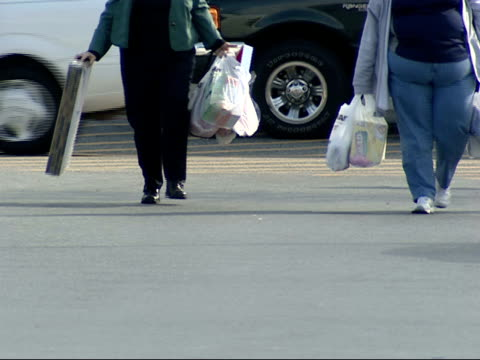 february 3 2006 ms two shoppers walking across parking lot with full bags / laurel maryland united states - laurel maryland stock videos & royalty-free footage